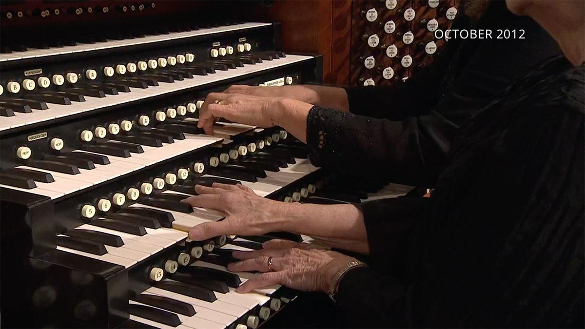 dois pares de mãos tocam no teclado do órgão