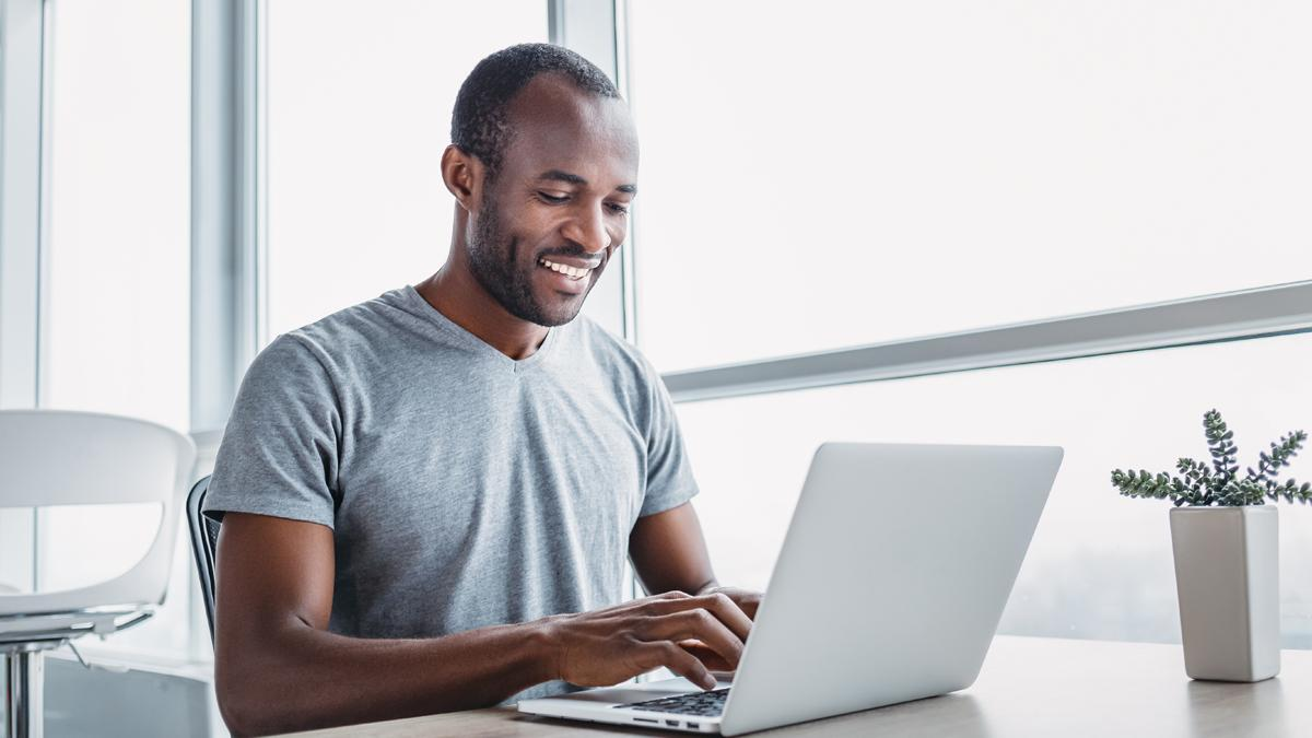 Un uomo sorridente è seduto e usa un computer portatile.
