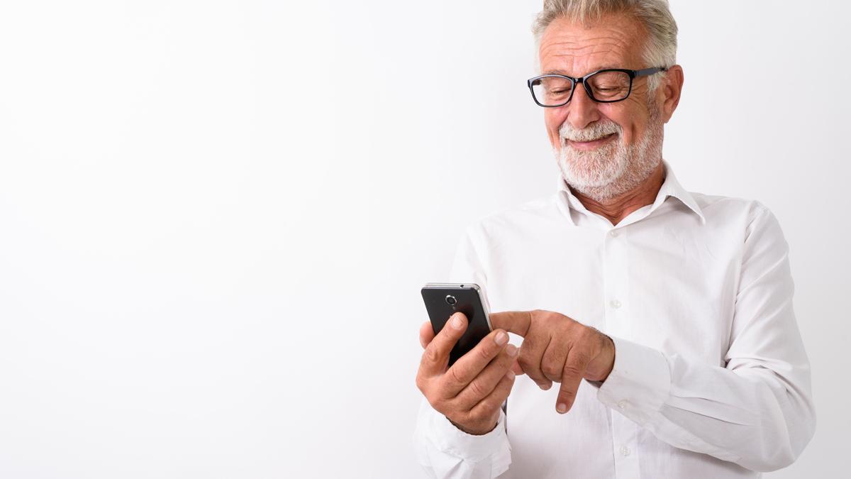 Um homem idoso a sorrir de pé, a usar um telemóvel.