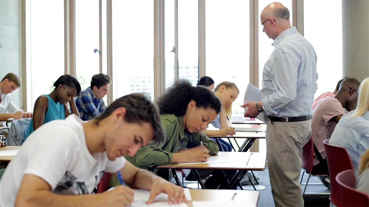 A group of students sit taking an exam.