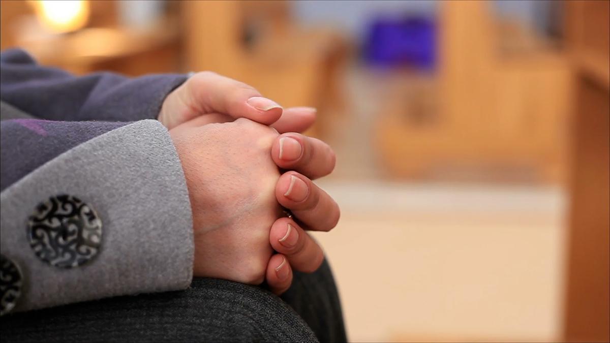 Kädet yhteen liitettyinä rukoukseen.