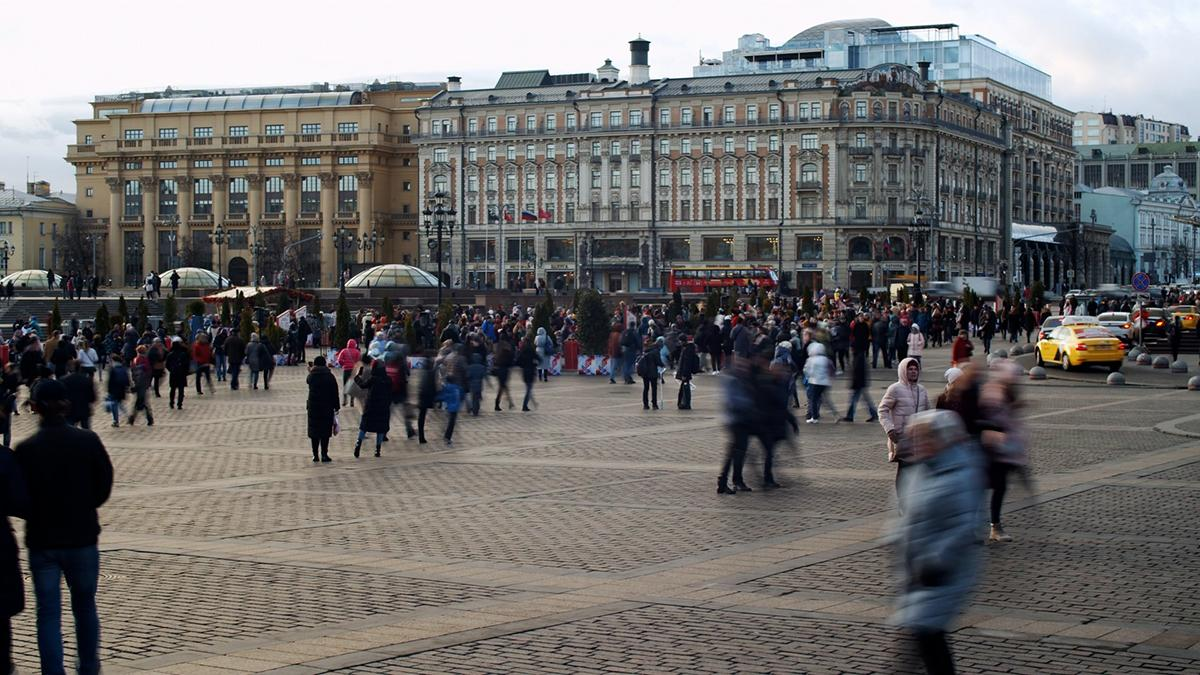 Uma praça da cidade cheia de pessoas.