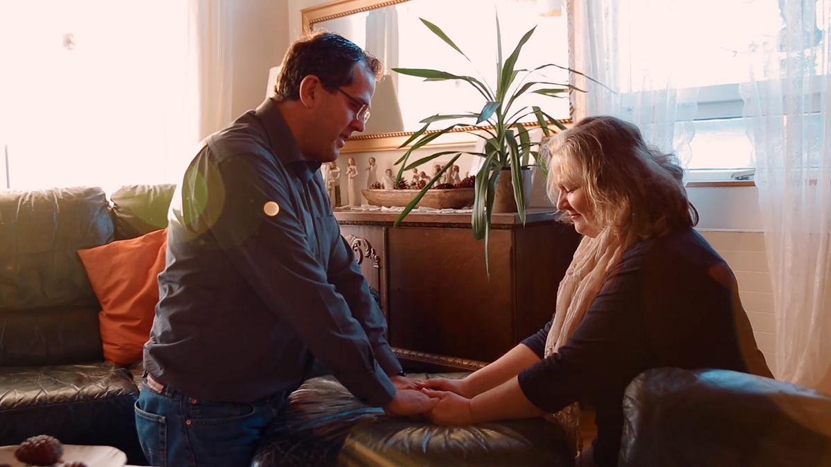 Pariskunta polvistuu yhdessä rukoukseen.