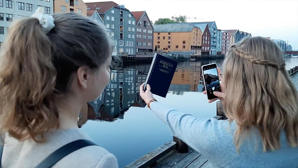 2 sister missionaries taking pictures