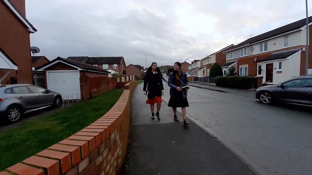 2 sister missionaries walking in the street