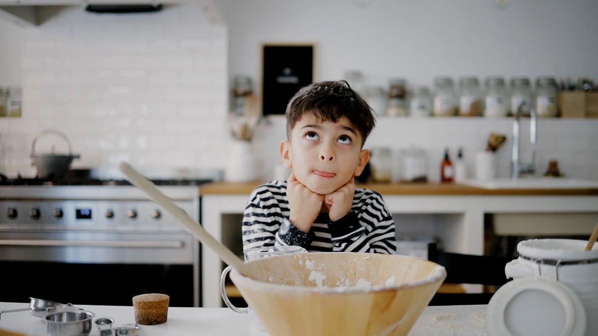 Mały chłopiec siedzi sam w kuchni.