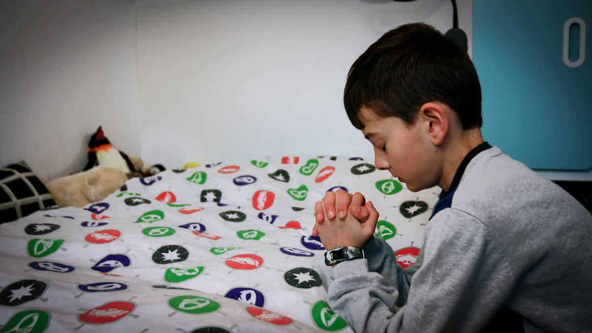 A young boy kneeling in prayer