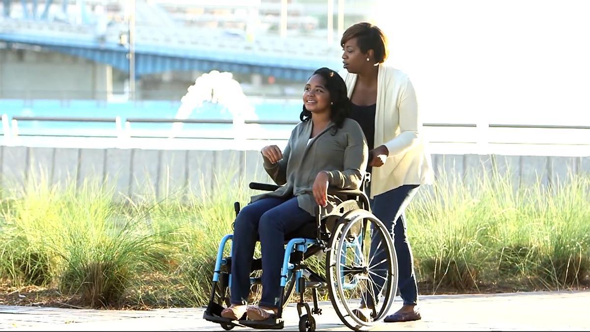 kobieta pcha wózek inwalidzki, na którym siedzi jej przyjaciółka