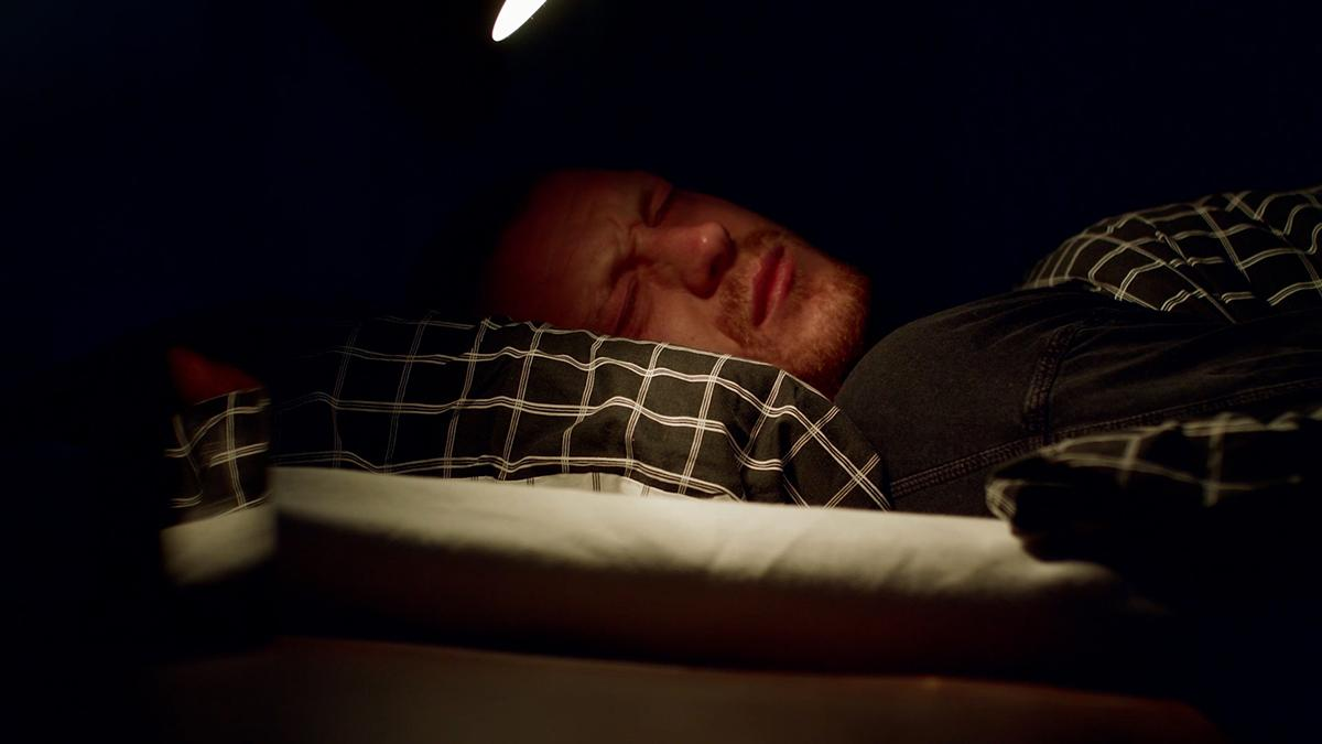 En man som ligger i en säng.