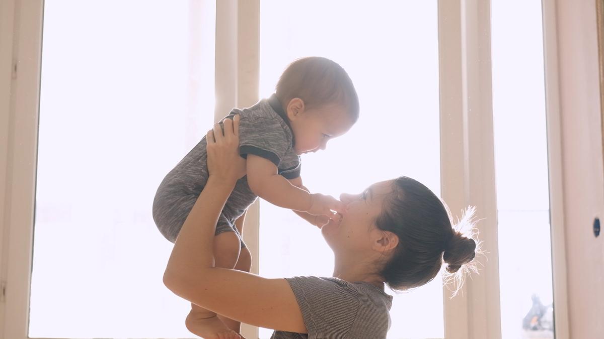 Eine Frau hebt ein Baby hoch zu ihrem Gesicht