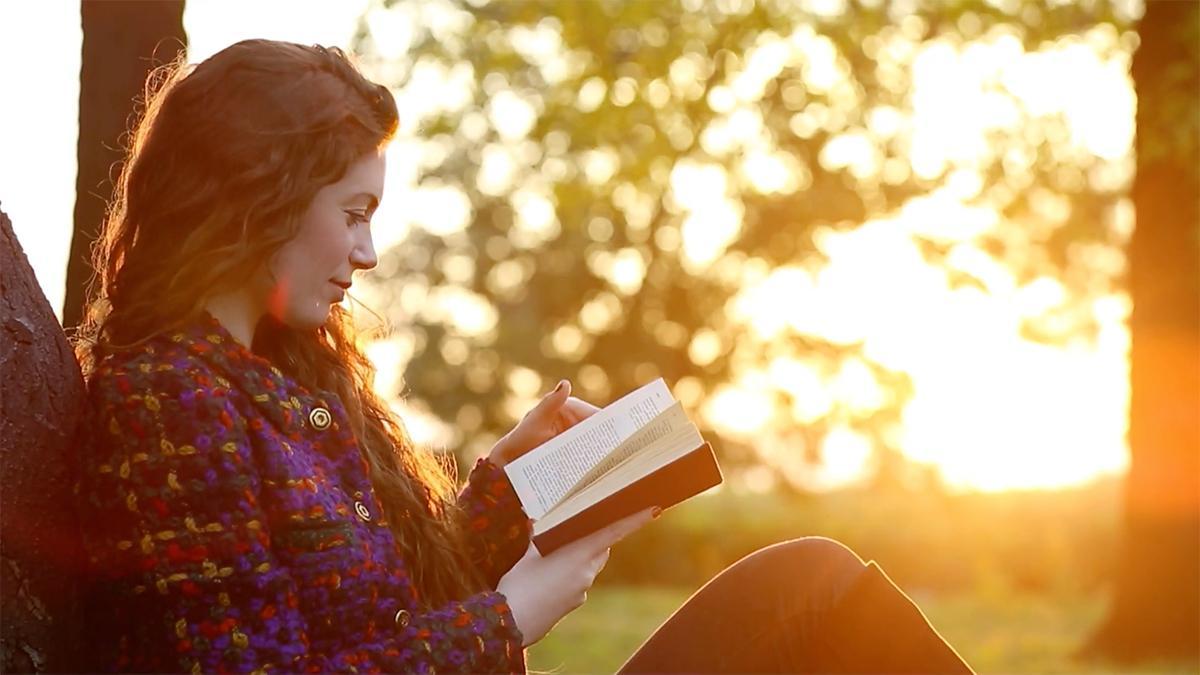 uma jovem mulher senta-se e lê num livro