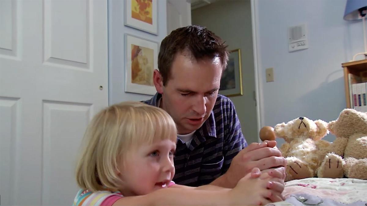 um pai ajoelha-se com a sua filha em oração