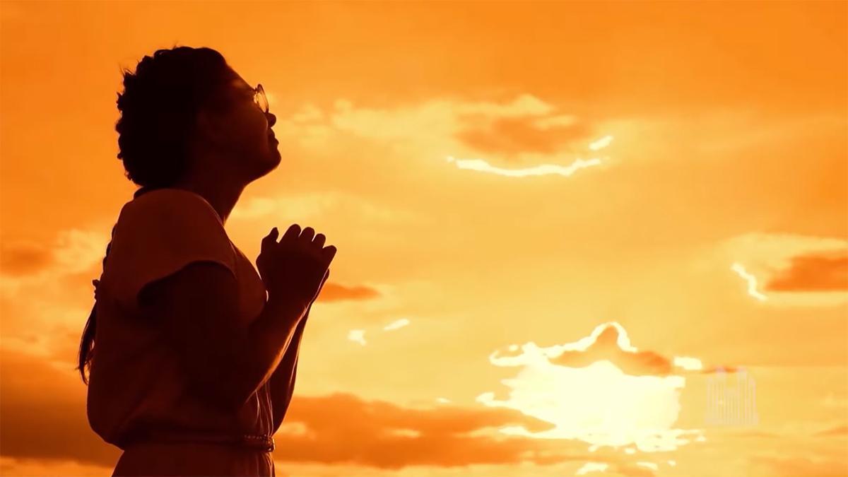 uma jovem mulher olha para um pôr-do-sol laranja