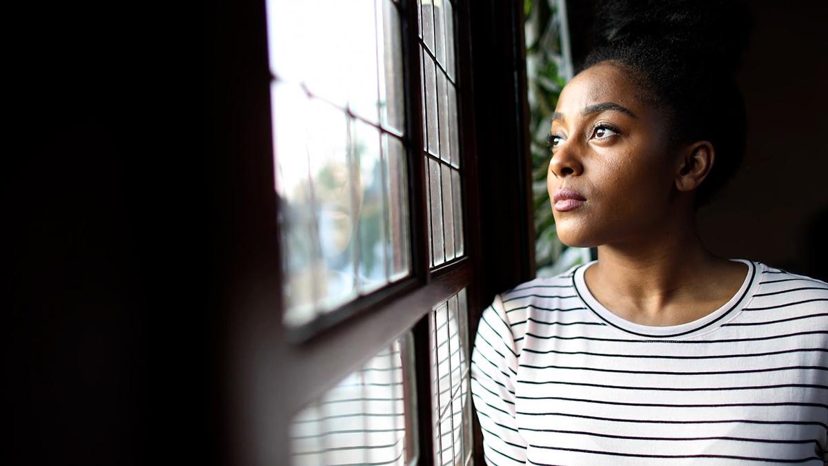 Een vrouw kijkt mijmerend door het venster.