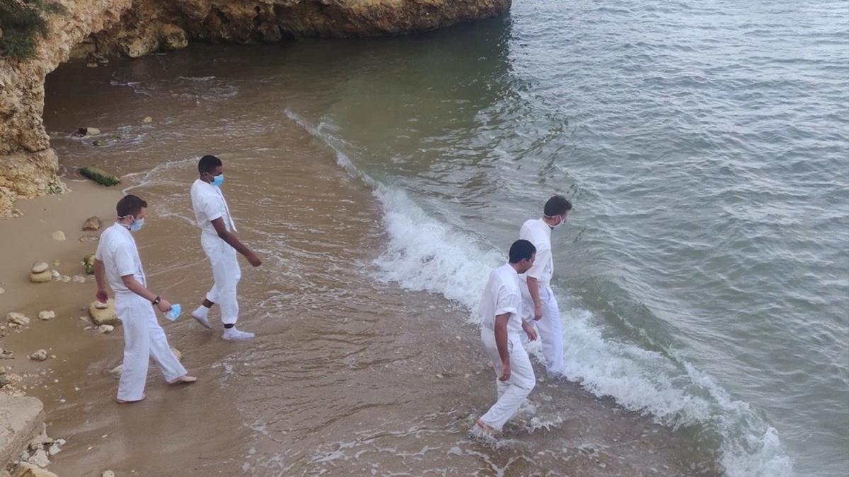 Four men walking into the water to do baptisms.