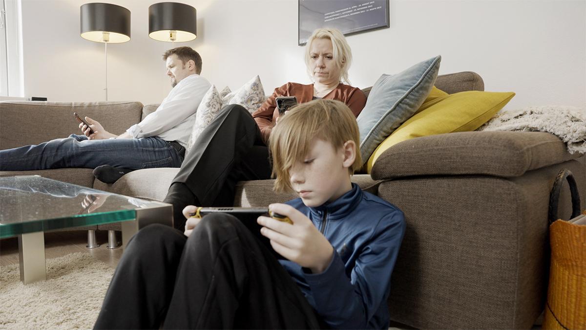 Чланови породице седе и гледају у своје телефоне.