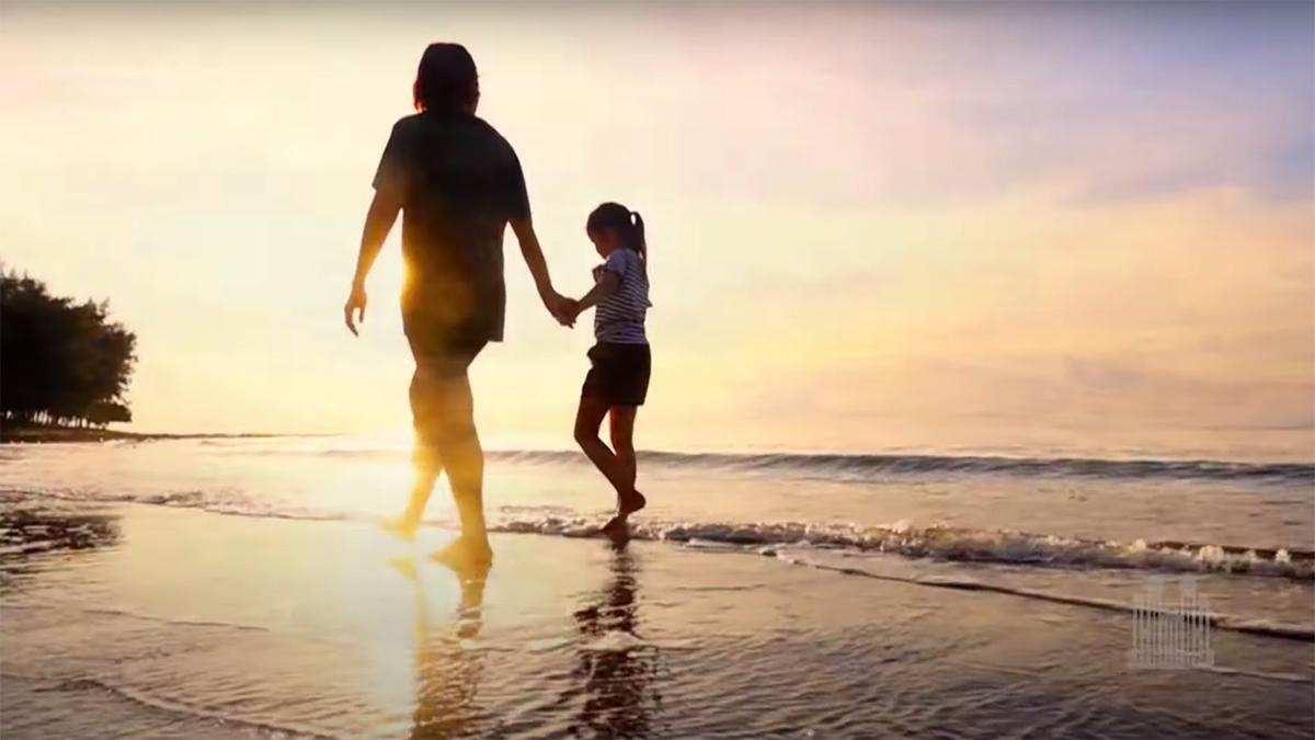 Uma mãe segura o seu filho pela mão enquanto caminham pela praia
