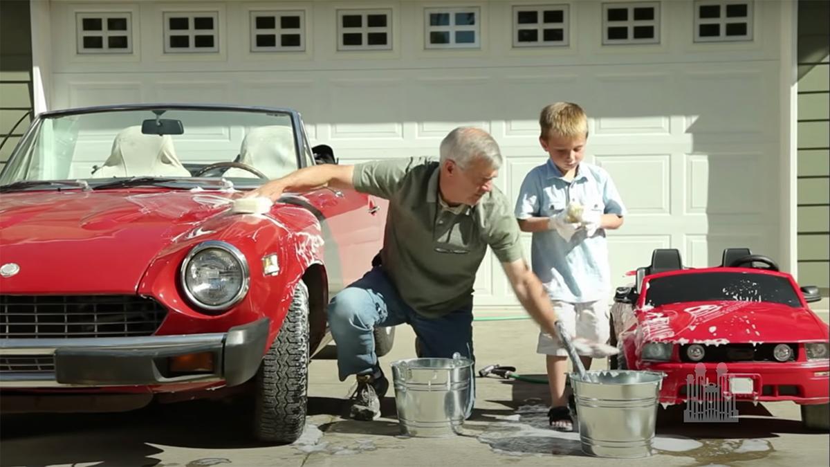 Um avô e um neto lavam juntos os seus carros