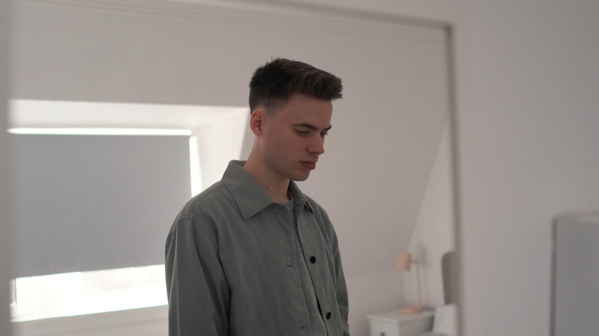 Een jonge man is in zijn slaapkamer in gedachten verzonken.