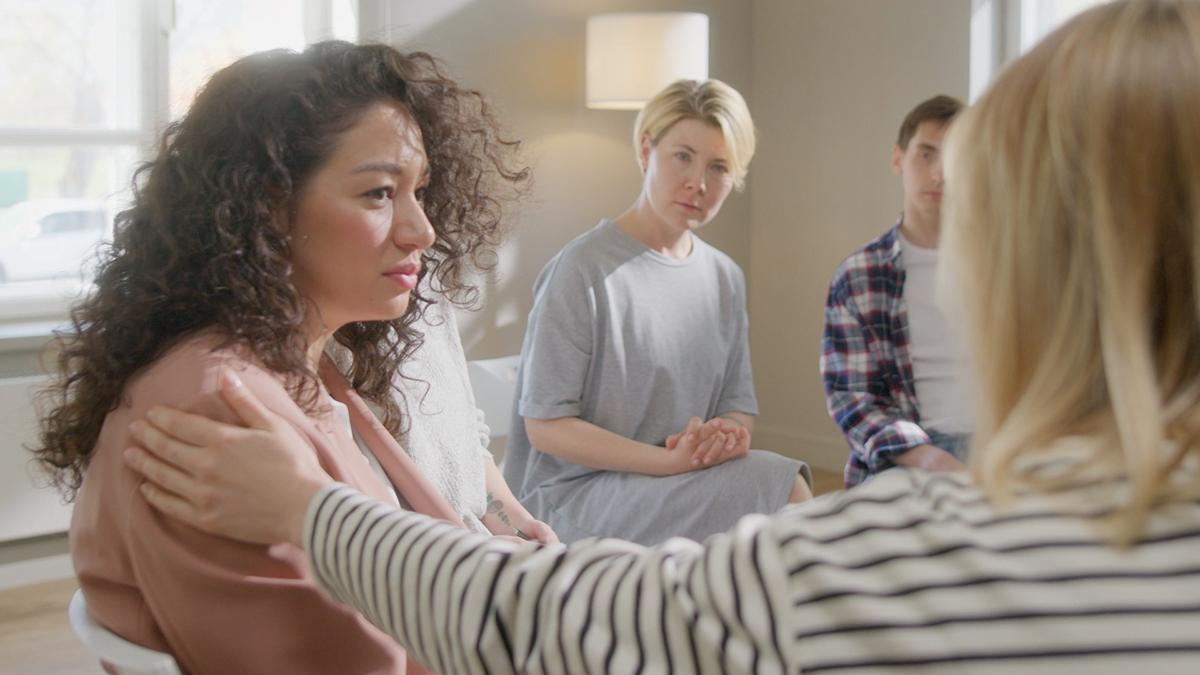 Una donna viene consolata da un'amica in un gruppo di sostegno.