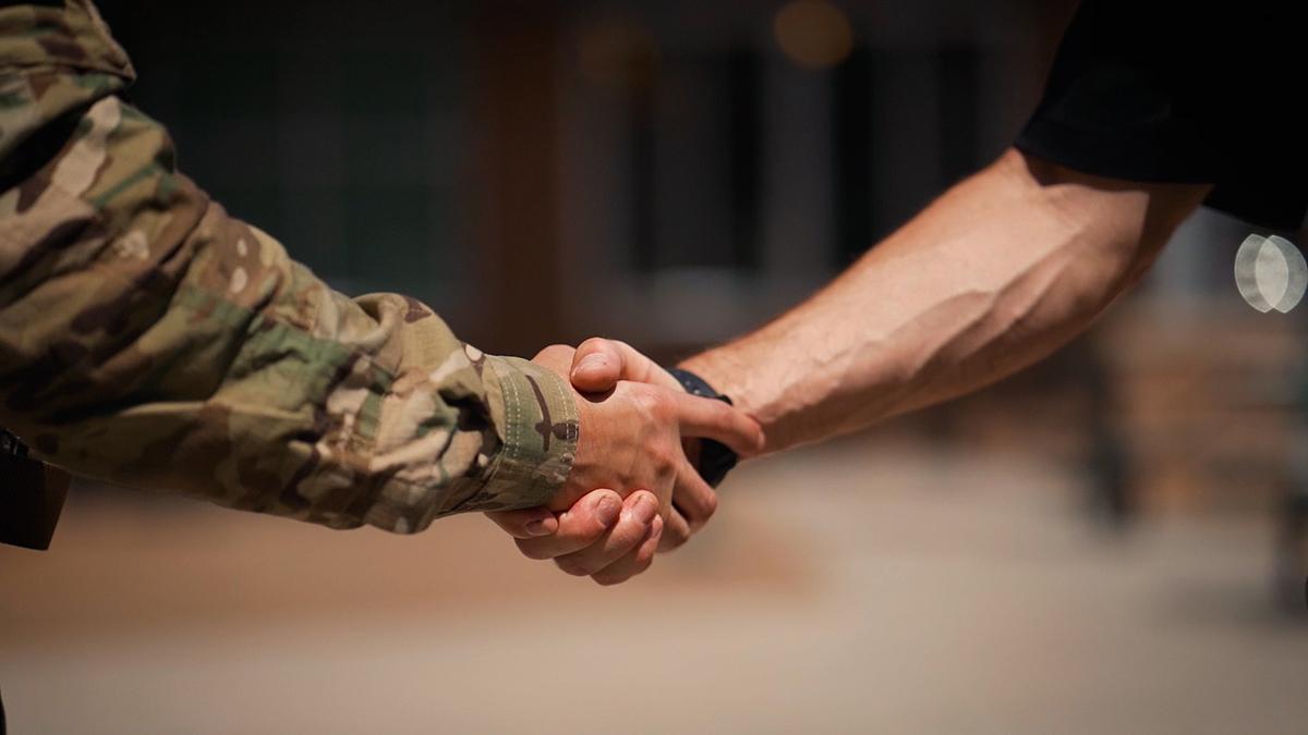 Een soldaat en een burger schudden elkaar de hand.