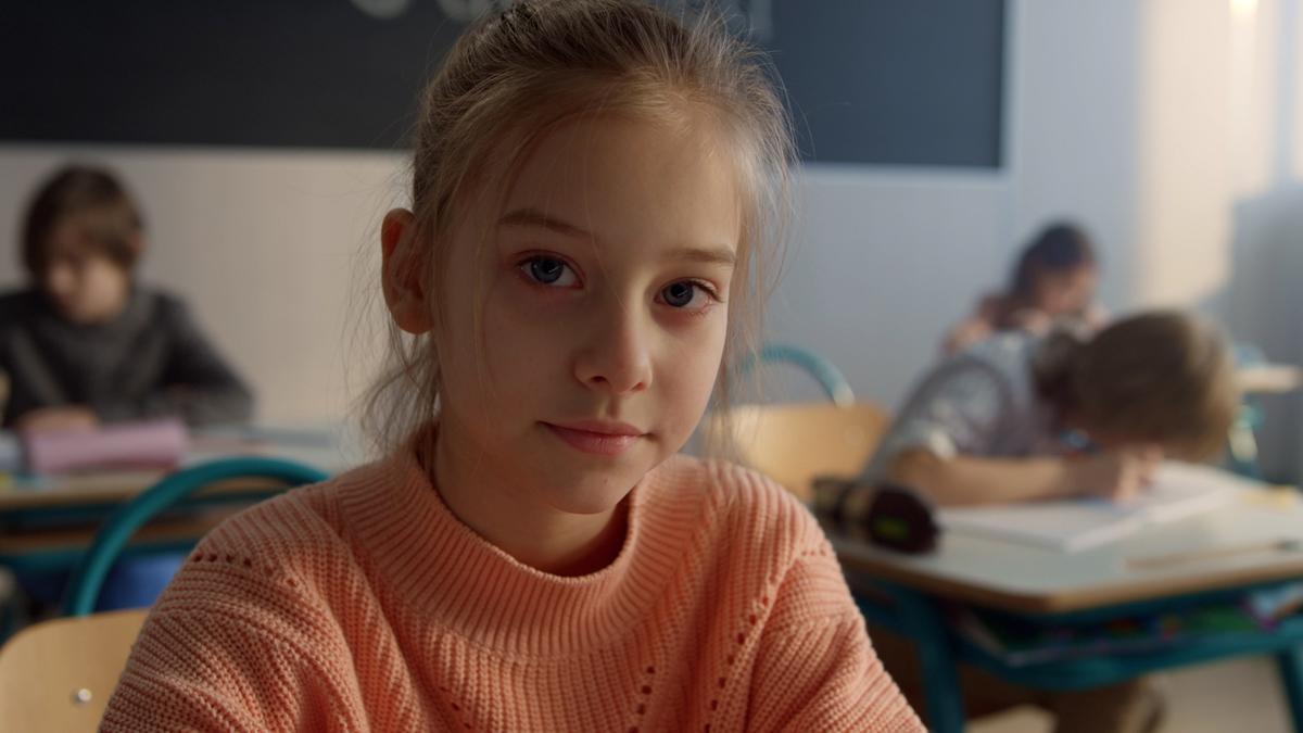 Девојчица седи за школском клупом и гледа у камеру.