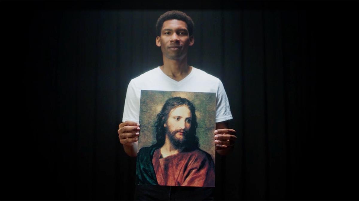 um homem segurando uma foto de Cristo