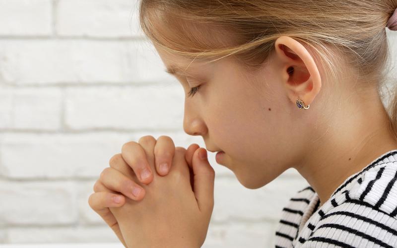 Una niña orando.