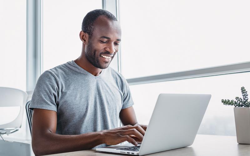 Ein Mann sitzt lächelnd an einem Laptop