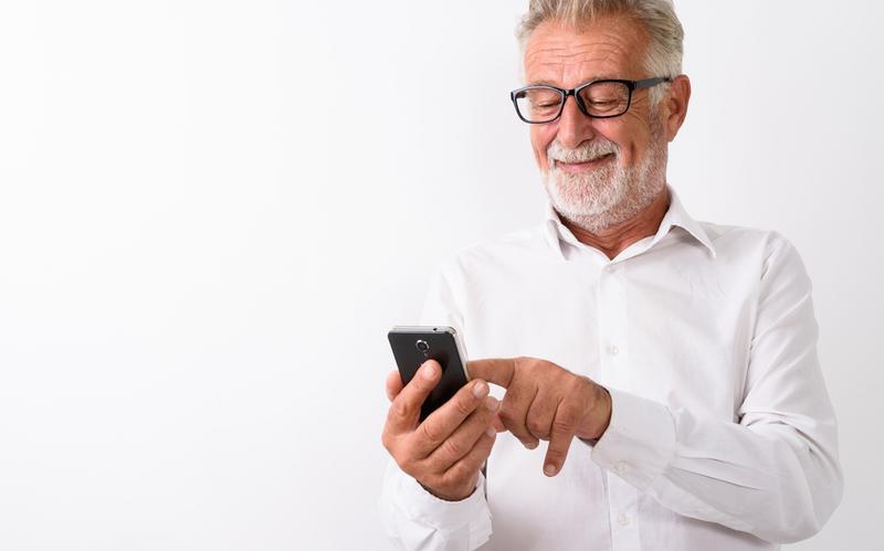 Nasmiješeni stariji muškarac stoji i koristi mobitel.