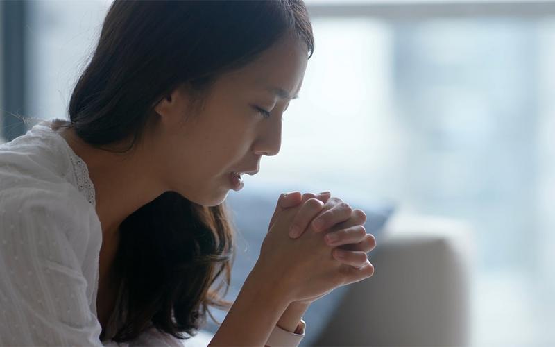 Una giovane donna inginocchiata in preghiera.