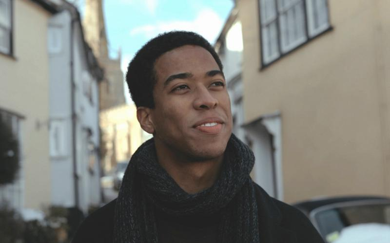A young man smiling and looking upward.