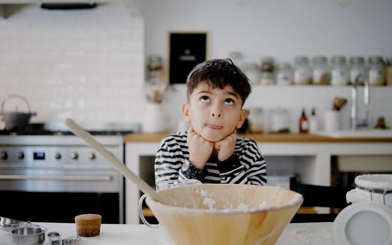 A young boy sits alone in the kitchen.