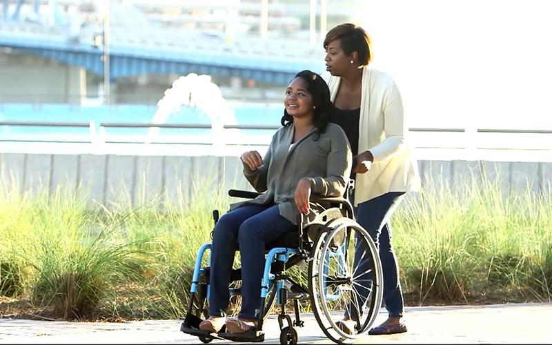 a lady pushes a wheelchair in which a friend of her sits
