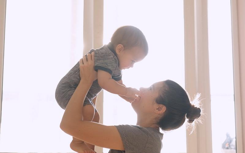 En kvinde holder et spædbarn op til sit ansigt