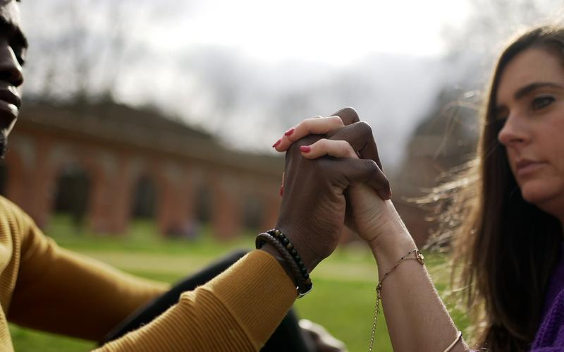Una pareja multirracial cogida de la mano.