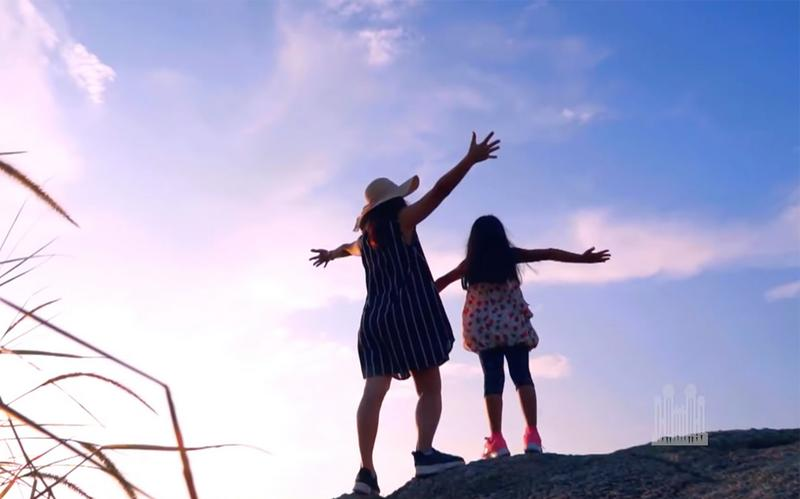 a mother and daughter stand with arms outstretched against a blue sky