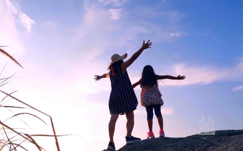 Eine Mutter und eine Tochter strecken ihre Hände zum blauen Himmel aus