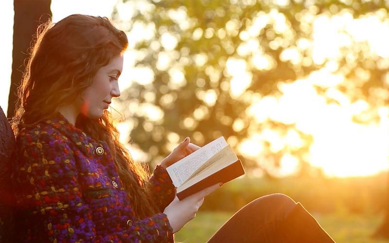 una mujer jóven sentada lee un libro