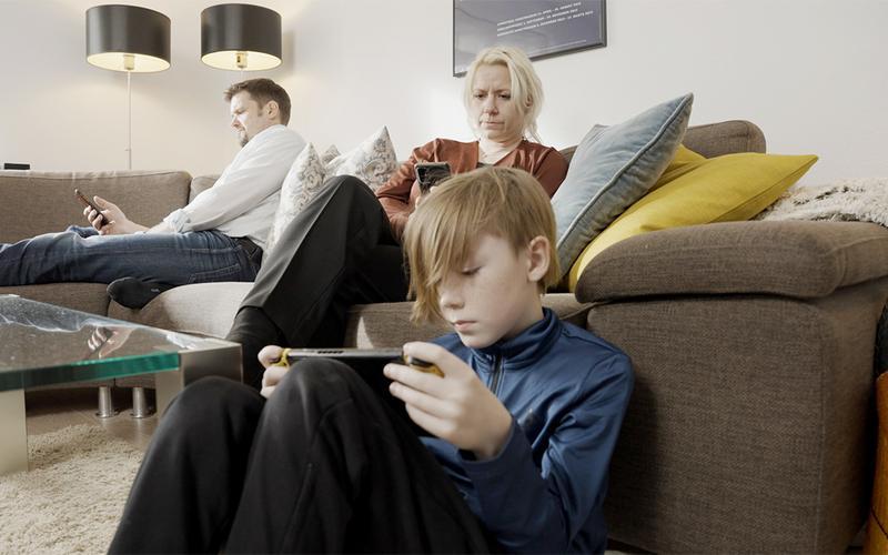 Uma família sentada a olhar para os seus telemóveis.