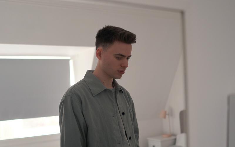 En ung mann står i dype tanker på soverommet.