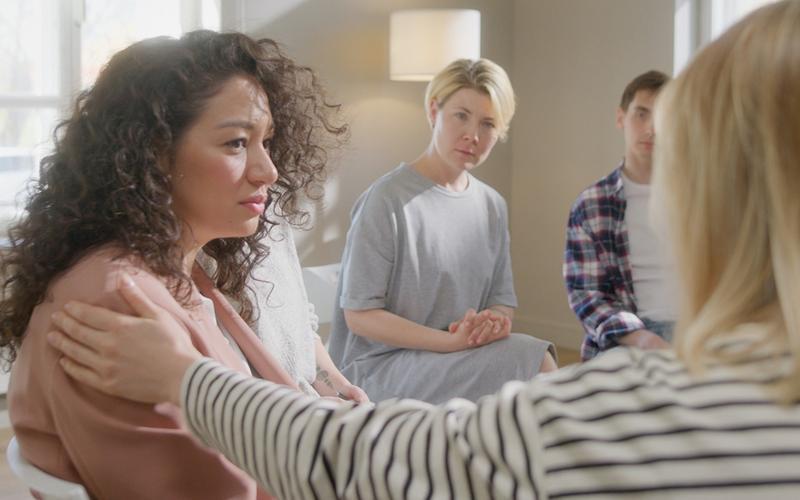 Uma mulher é consolada por uma amiga num grupo de apoio.