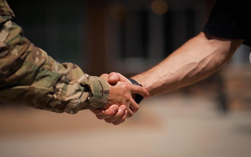 Um militar e um civil cumprimentam-se apertando as mãos.