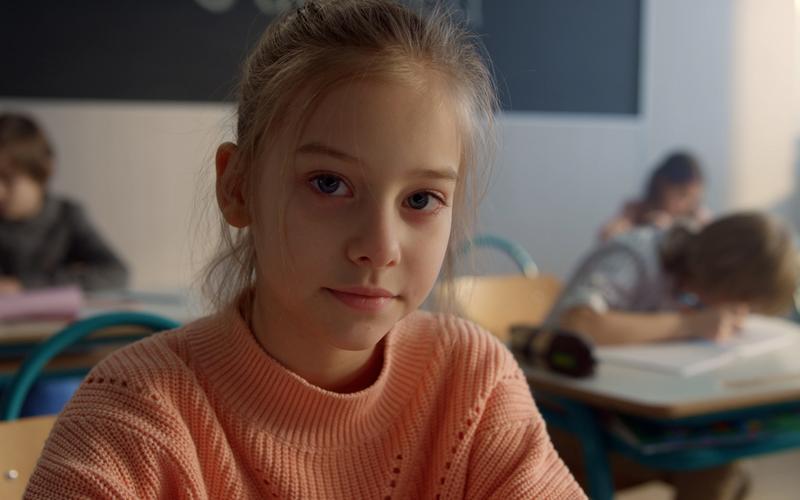 Uma menina sentada à secretária da escola a olhar para a câmara.