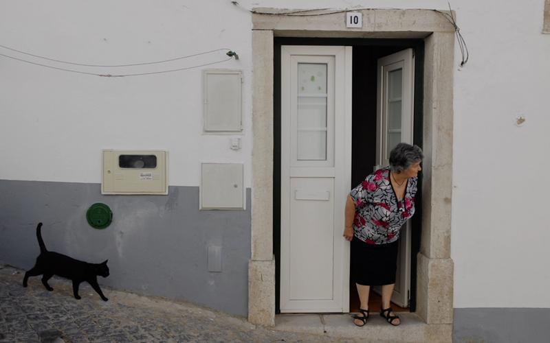 Një grua e moshuar qëndron e pështjelluar te pragu i derës së saj.