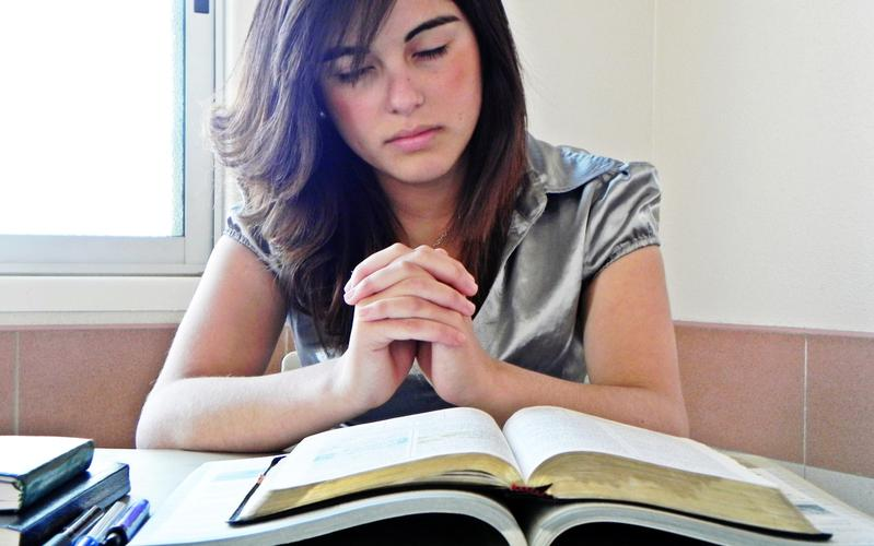 a girl is reading and praying