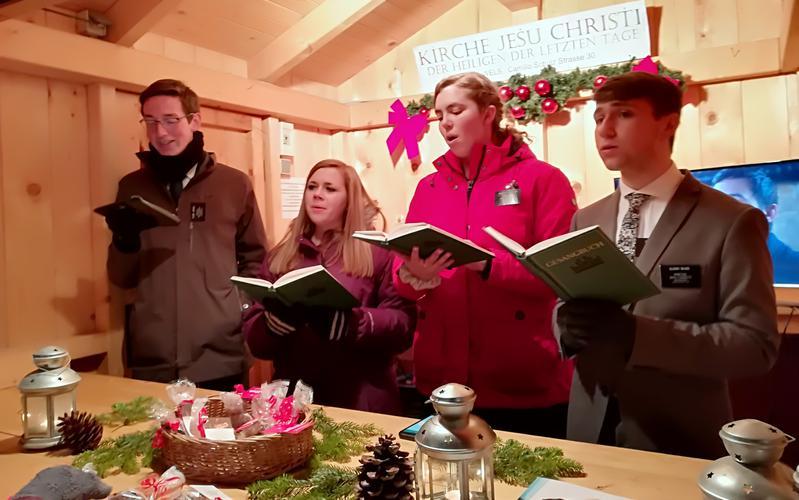 Junge Damen und Missionare singen am Adventmarkt