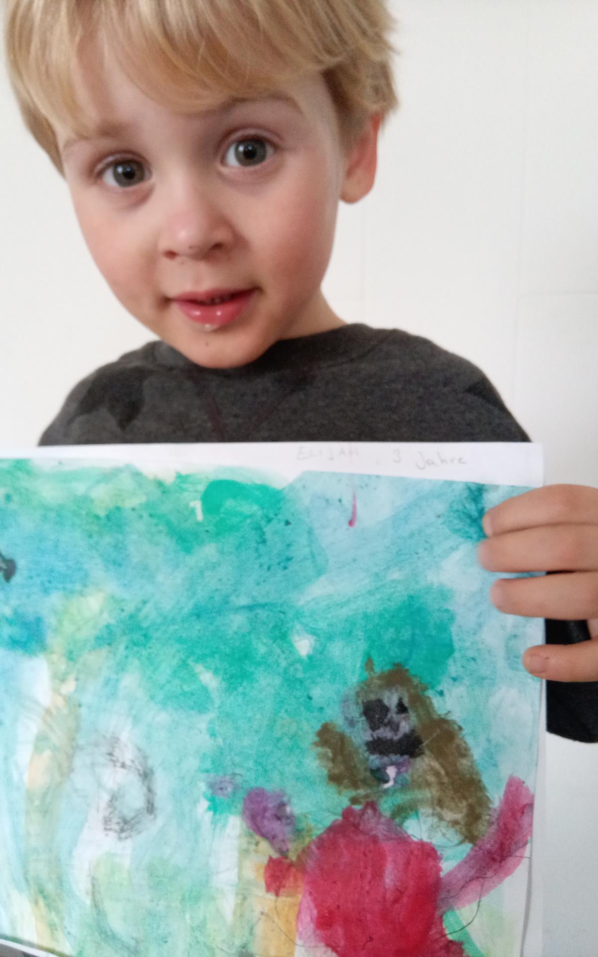 Der dreijährige Elijah präsentiert sein kleines Kunstwerk