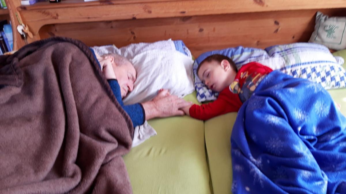 Herr Schweighuber schlafend, wie er die Hand seines Enkelsohnes sanft umschlungen hält.