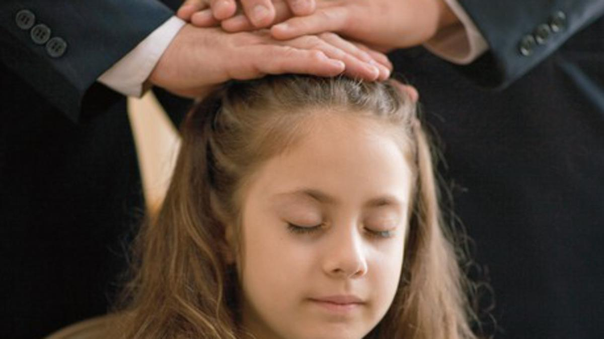 Ein Mädchen erhält nach der Taufe mit Wasser die Gabe des Heiligen Geistes durch Händeauflegen